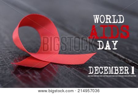 Aids Awareness campaign. Red ribbon on wooden background for World Aids Day concept.