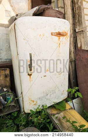 The refrigerator stands among the trash on an abandoned site. A refrigerator which is long overdue to change.