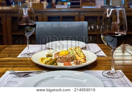 Close up of a fresh beef tartar with egg yolk, with mustard marmalade, anchovies and corn baguette. with a glass of wine on the table in the restaurant