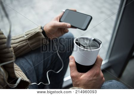 Man Holding Thermos Cup And Smartphone
