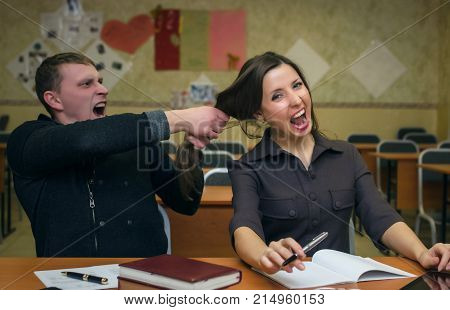 Students quarrel at the lesson and fool around. Angry student guy pulls by the hair a young student girl. Education.