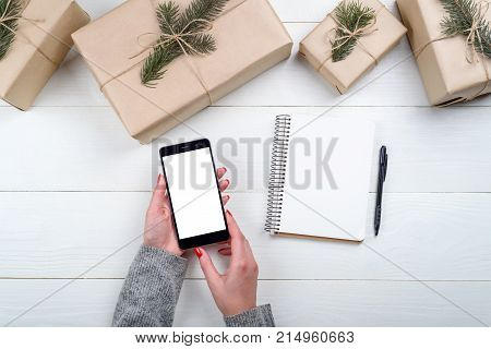 Female hands with mobile smart phone with blank screen for app presentation copy space. Christmas gifts and blank notebook on white wooden background. Flat lay top view. Application mockup template