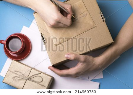 A man signs a gift. Mail. Card.