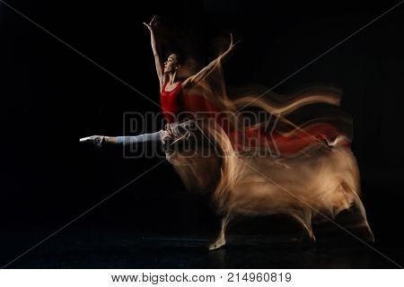 Professional performance. Attractive nice female dancer standing against black background and showing her skills while performing