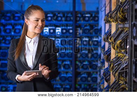 Beautiful woman at mining farm. Virtual money concept. Cryptocurrency