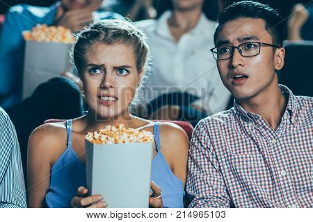 Terrified people, young and senior Asian men and young Caucasian woman, sitting in cinema watching thriller. Young woman holding popcorn