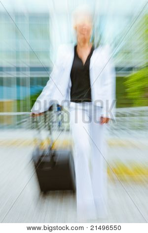 Rushing modern business woman with suitcase walking on street. Motion blur