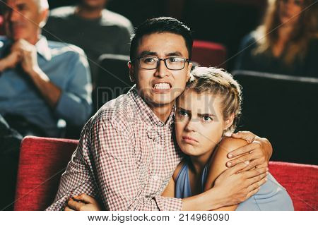 Fearful young couple hugging tightly when watching horror film in cinema. Multi-ethnic couple watching scary scene in movie. Terrified viewers concept