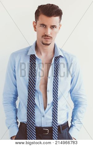 Closeup of disappointed young handsome business man looking at camera, wearing unbuttoned shirt and standing with hands in pockets. Isolated view on white background.