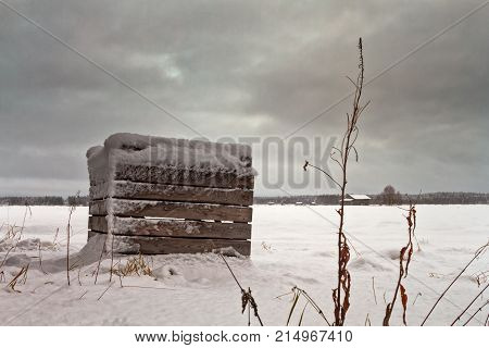 The snow covered everything on the fields of the Northern Finland over one night. The wooden potato crates look abandonded on the white snow.