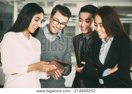 Middle-aged Indian woman holding tablet computer and showing its screen to interested colleagues. They are standing with blurred view in background.