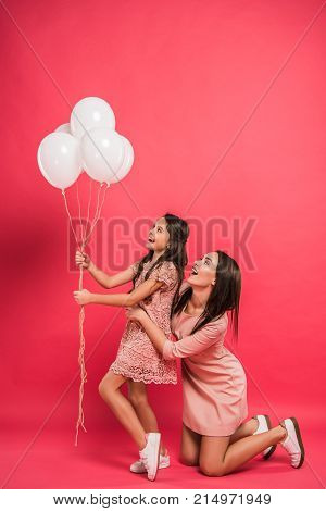Daughter And Mother Looking At Balloons