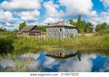 Evicted old wooden houses on the shore of muddy pond in the summer