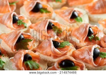 Cropped clos up of buttered canapes with smoked salmon decorated with black olives eating food tasty meny serving delicacy gourmet cafe restaurant appetite hunger concept. poster