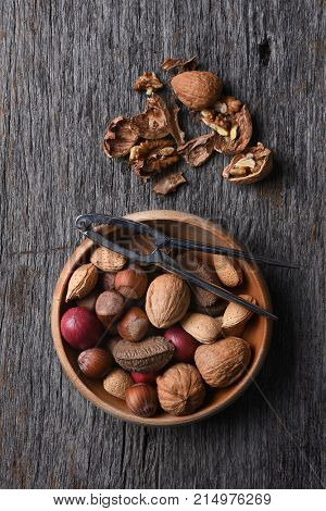 Overhead view of a bowl of mixed nuts with nutcracker and cracked nuts on a rustic wood table.