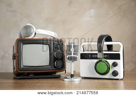 Retro portable TV, radio, microphone and headphones on table against light wall