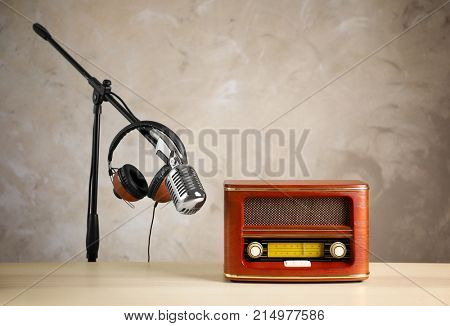 Retro radio, headphones and microphone on table against light wall