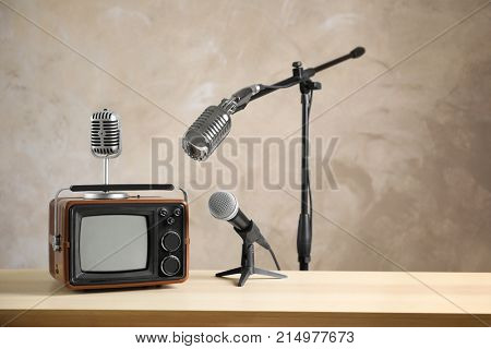 Retro portable TV and microphones on table against light wall