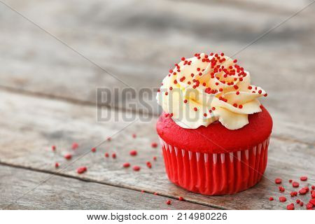 Delicious red velvet cupcake on table