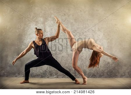 Two person, dancers, woman and man in dynamic action figure pose under light on the grunge background.