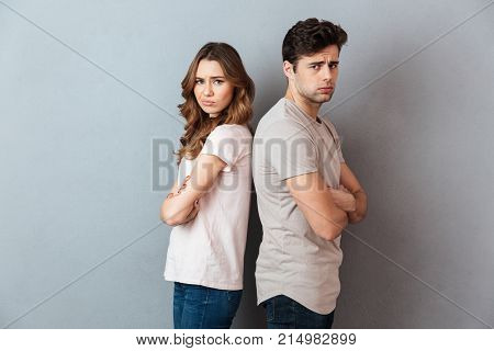 Portrait of an upset sad couple standing back to back and looking at camera over gray wall
