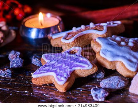 Candle light table with Christmas gingerbread cookies and cinnamon stick and star sweets are on wooden table and burning candles. Xmas still life object.