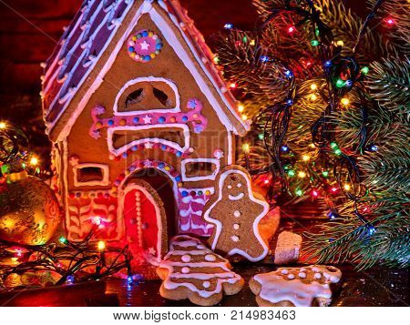 Ginger bread houses with Christmas garland. Xmas food gingerbread man cookies decorating holiday table burning candles.