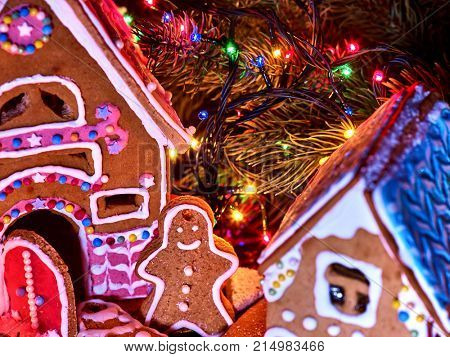 Ginger bread houses with Christmas garland. Cropped shot of Xmas food gingerbread man cookies decorating holiday village table with burning lights string.