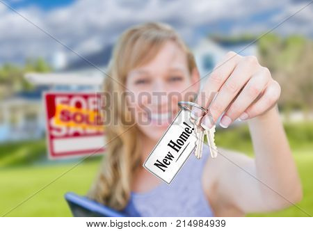 Woman Holding New House Keys with New Home Card In Front of Sold Real Estate Sign and Home.