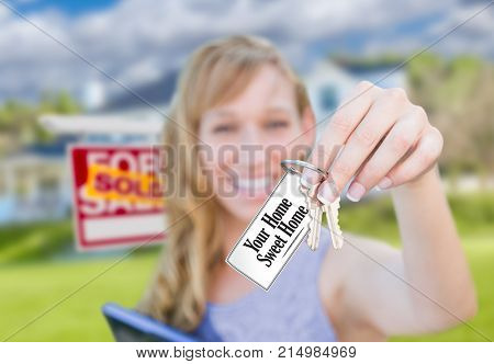 Woman Holding New House Keys with Your Home Sweet Home Card In Front of Sold Real Estate Sign and Home.