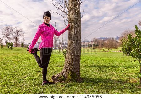 Young woman warming up and stretching the legs before running on a cold winter, autumn of fall day in an urban park. Female athlete wearing pink windbreaker, beanie, gloves and running tights