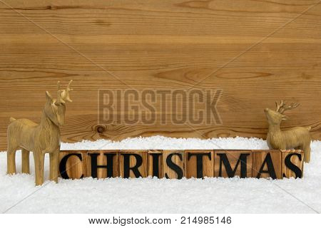 The word Christmas with two wooden reindeer in snow, copy space for you own message.