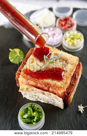 Restaurant Cold Starter Food - Delicious Fish Tartare with Spicy Sauce. Gourmet Restaurant Appetizers Menu. Fish Tartare Garnished with Crispy Bread