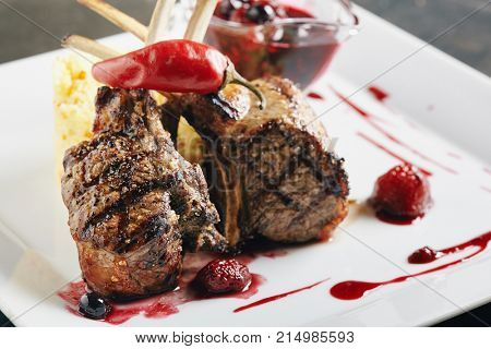 Grilled Restaurant Food - Rack of Lamb Barbecue with Garnish, Berry Sauce  on Black Stone Background