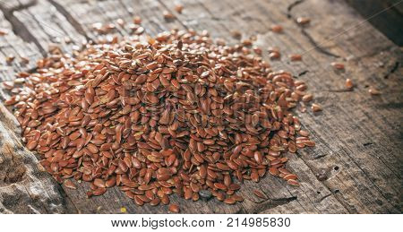 Heap of flax seeds or linseeds, on wooden surface.