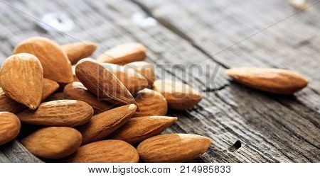 Almonds close up on an old wooden table, copy space