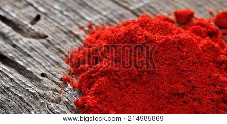 A heap of paprika powder, on a wooden table, copy space