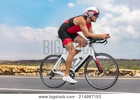 Triathlon cyclist man cycling racing on road bike on ironman competition racing against time. Triathlete training bicycle workout for triathlon race.