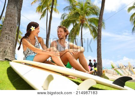 Hawaii surfers people lifestyle happy living couple talking on Waikiki beach relaxing from surfingwith surfboards in Honolulu city. Friends laughing having fun in Oahu island, USA travel lifestyle.