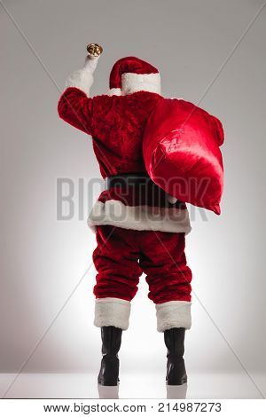 back view of santa claus ringing bell with bag on shoulder on grey background