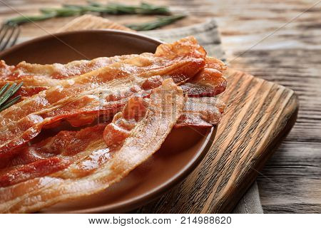 Plate with cooked bacon rashers on board, closeup