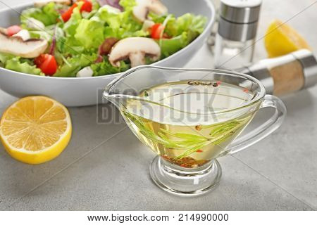 Gravy boat with tasty salad dressing on table