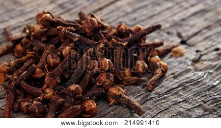 A heap of dried cloves on a wooden table, copy space