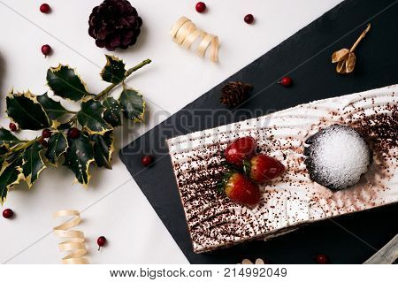 Christmas dessert. Fresh strawberry cake souffle cream and chocolate crumbs with christmas decorations, fir cones, holly tree and berry on black slate cake board on white table. Festive new year food