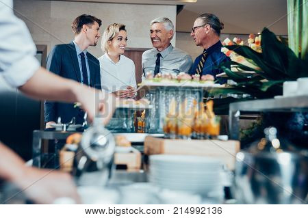 Distant four smiling business people chatting and standing at buffet table with food and blurred crockery and waiter in foreground
