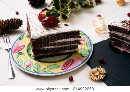 Delicious Christmas dessert. Cake with fresh strawberries . Slice of cake with souffle, strawberrie cream and chocolate crumbs with christmas decorations, fir cones, holly tree and berry on white background