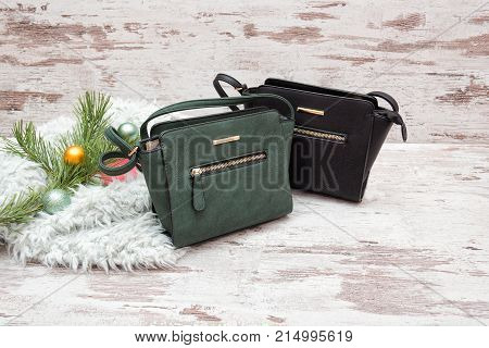 Green And Brown Female Handbag On A Wooden Background, Spruce Branch With Ornaments. Fashionable Con