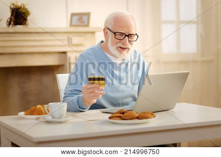Want to buy. Handsome mature man smiling and holding credit card while going to pay all orders