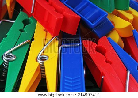 Colorful forecaps tweezers clips as background. Clothespin clothes pin colorful clothespeg red yellow blue clothes peg as wallpaper texture pattern.. Rainbow background.
