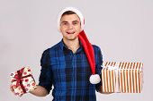 An inspired young man in a Santa Claus hat and in a checkered blue shirt smiles and holds a gift in both hands, looks into the camera. poster